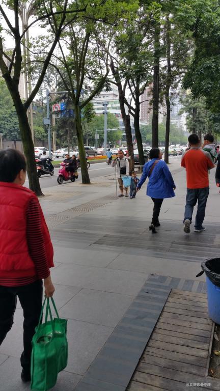 一个盲人乞讨者,牵着一个小男孩